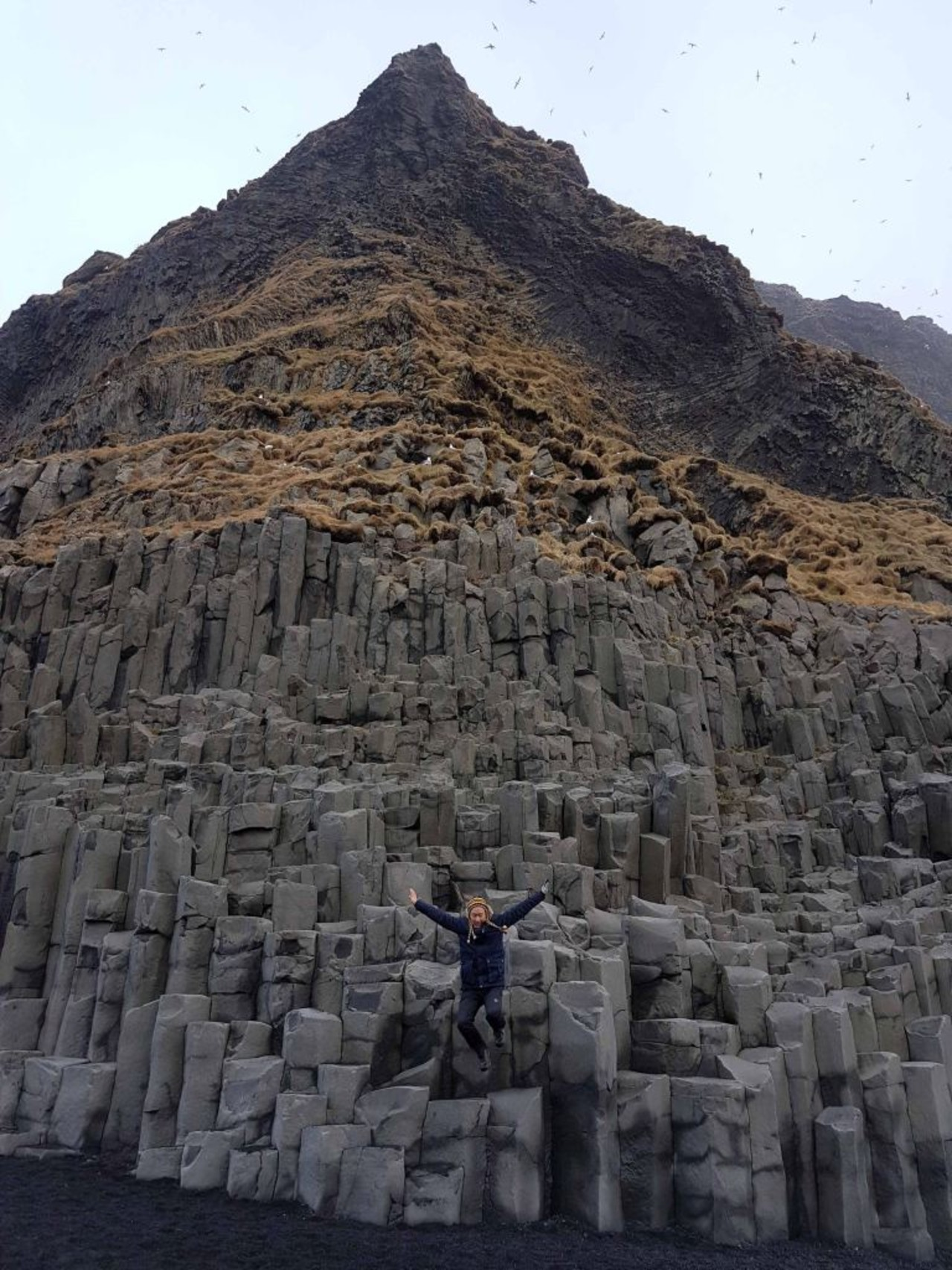 A woman jumping of a basalt columns at Reynisfjara in South Iceland