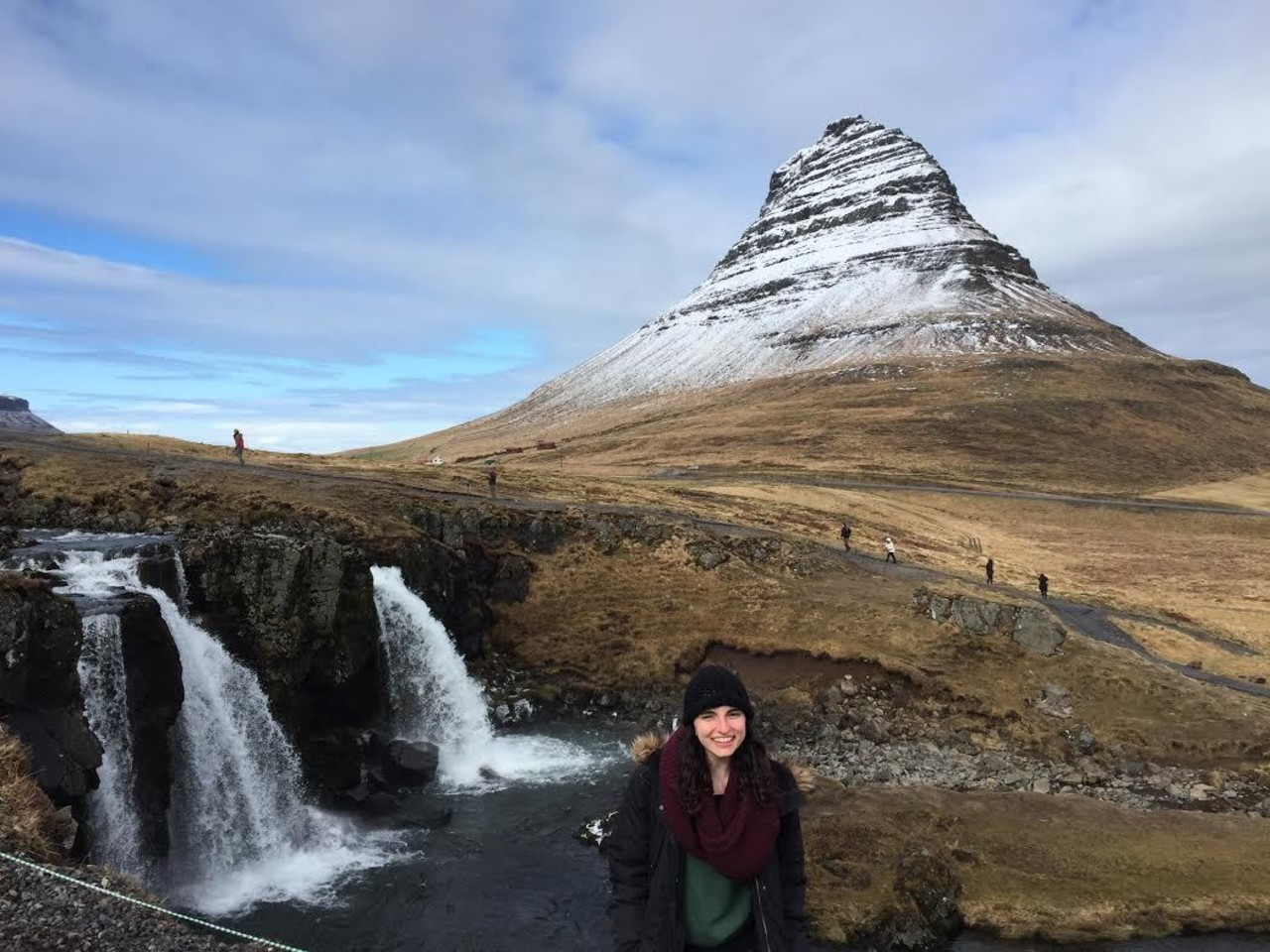 Sydney, Adventurer of the Week, is on Snæfellsnes peninsula posing for a photo in front of  waterfall and Kirkjufell mountain