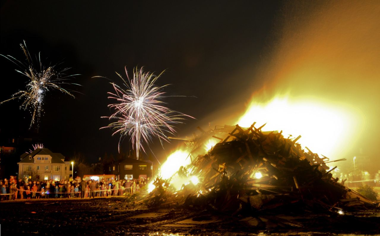 Bonfire on New Years Eve with fireworks and people watching