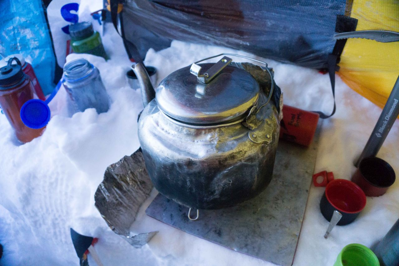 Water being boiled in a kettle in the snow in a tent on a glacier on a polar training course with Icelandic Mountain Guides