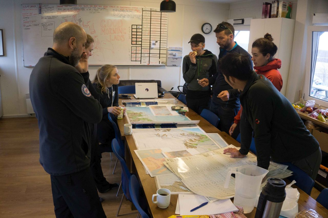 A group of people standing by tables looking at maps on a polar training course with Icelandic Mountain Guides