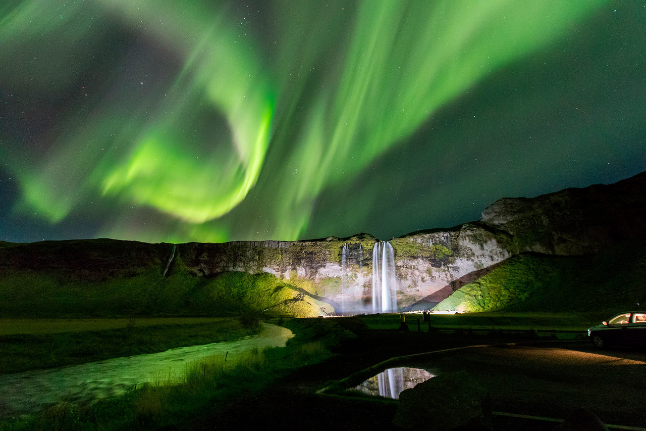 Green Aurora Borealis Over Seljalandfoss Waterfall. Winter Is The Best Time  To Visit Iceland To