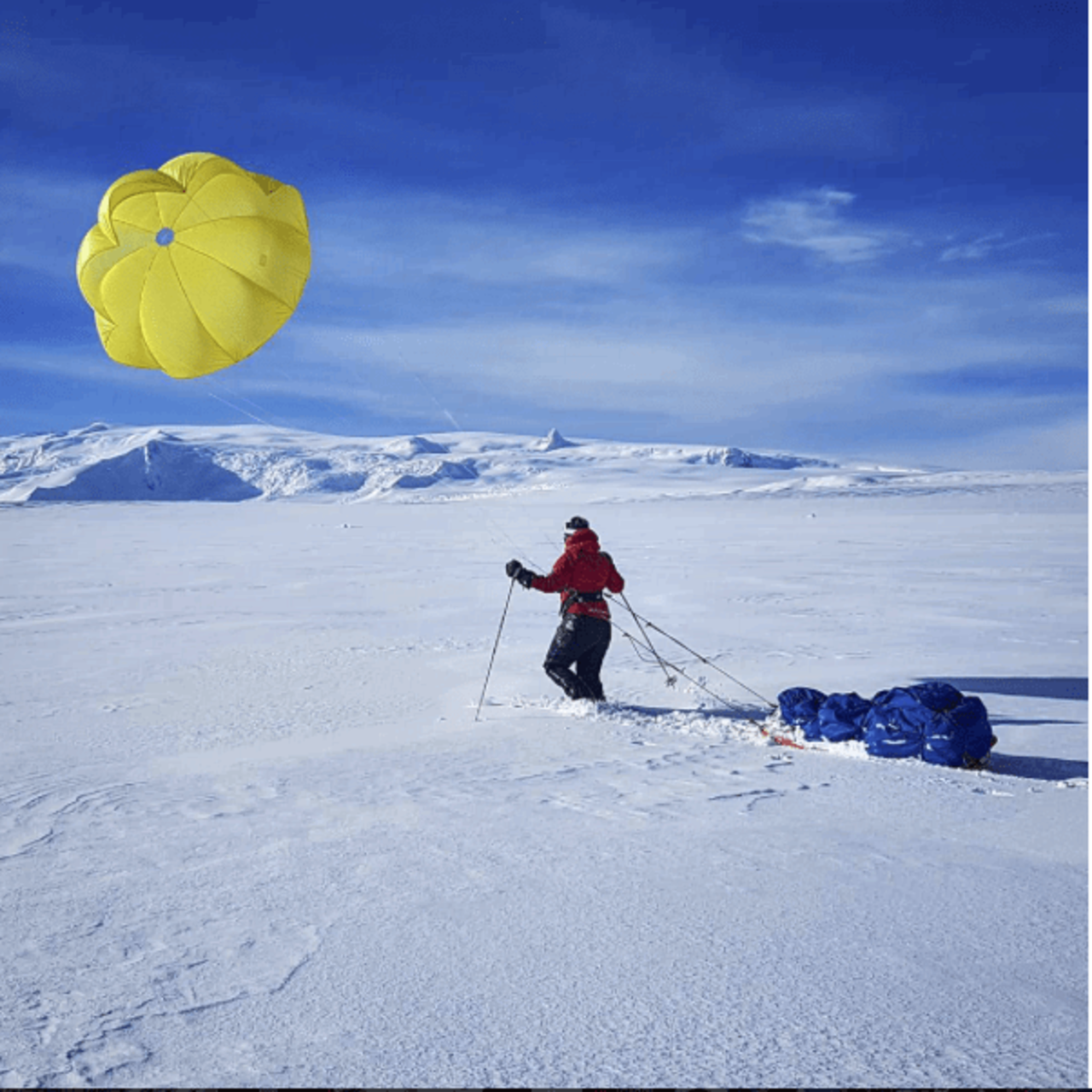 Mountaineer walking across glacier with a pulka and a kite on a course with Icelandic Mountain Guides.