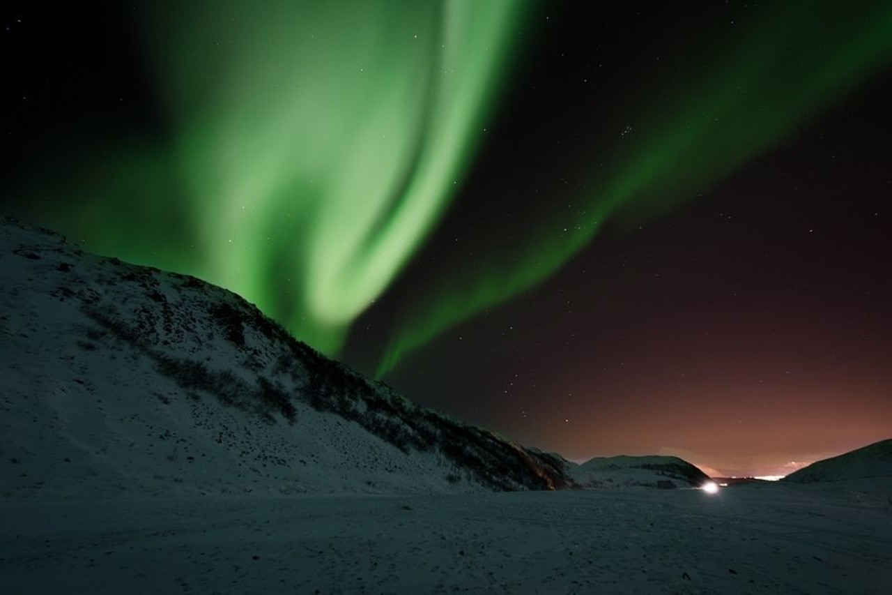 Green Iceland Northern Lights (Aurora Borealis) dancing in a dark sky above a snowy hill