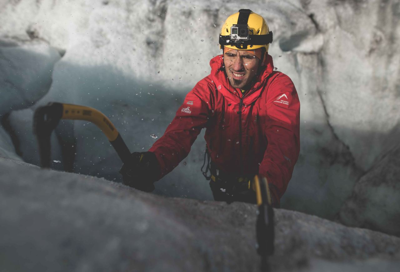 A man wearing a yellow helmet climbing an ice wall using rops and an iceax