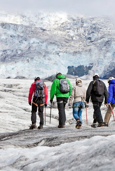 Group of hikers on the glacier going deeper into the valley towards the icefall