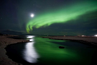 Beautiful bright green Northern Lights dancing in the sky and reflecting in lake it is winter time in Iceland