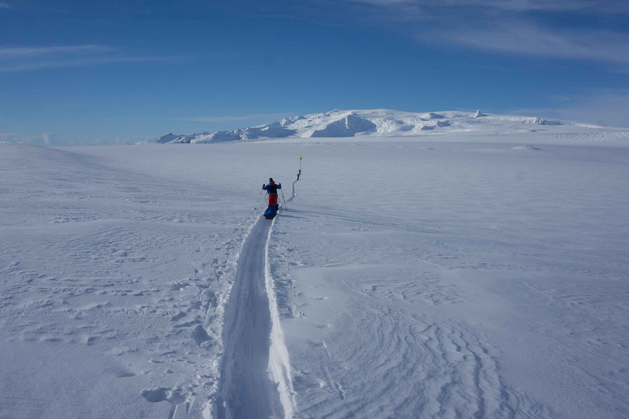 A group crossing a glacier on cross country skis with pulkas on a sunny day on a course with Icelandic Mountain Guides