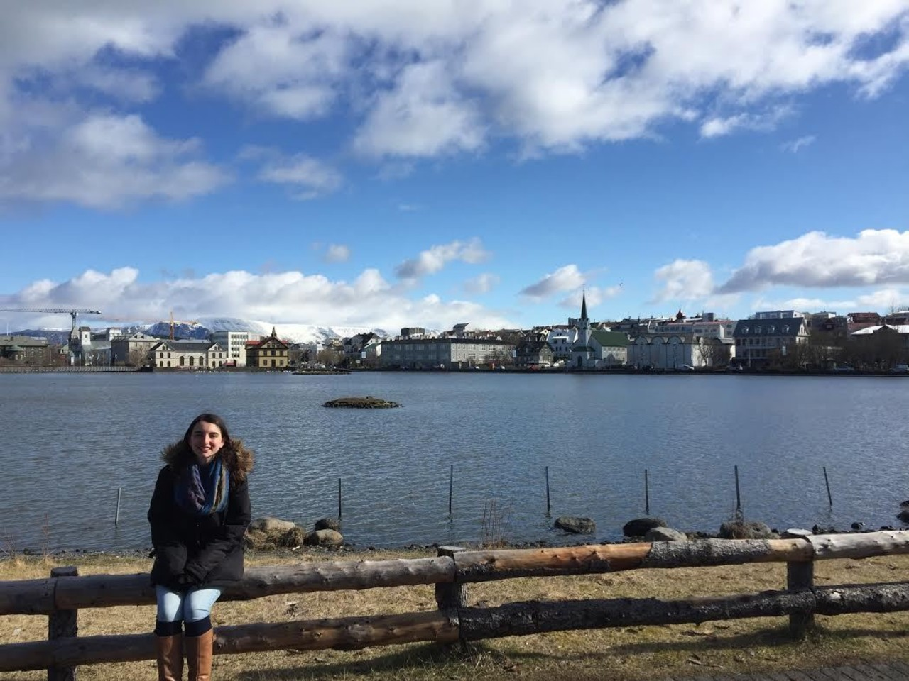 Sydney, Icelandic Mountain Guide's Adventurer of the Week, is sitting by the shore with a blue sky and buildings in the background.