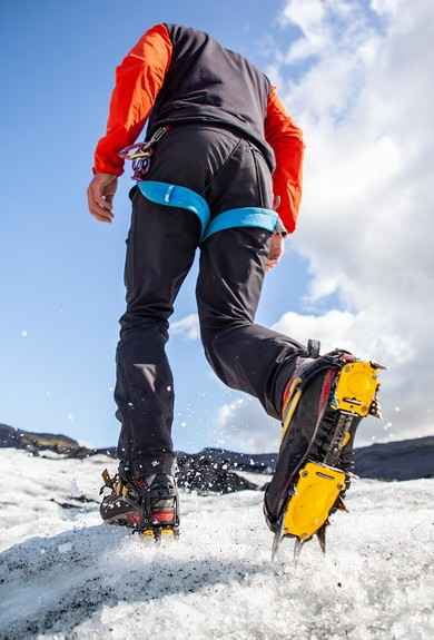 A man walking on glacier ice using crampons