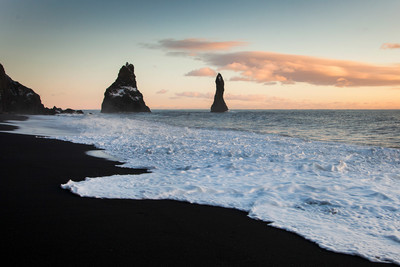 Reynisfjara black sand beach with huge stones in the water at dusk along the south coast of Iceland