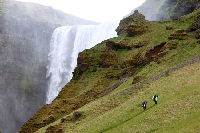 Two people hiking next to a big waterfall
