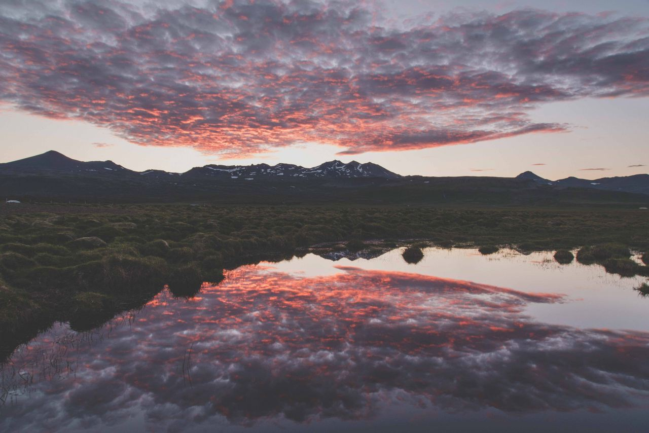 Pink and orange clouds reflecting on water with mountains in the distance