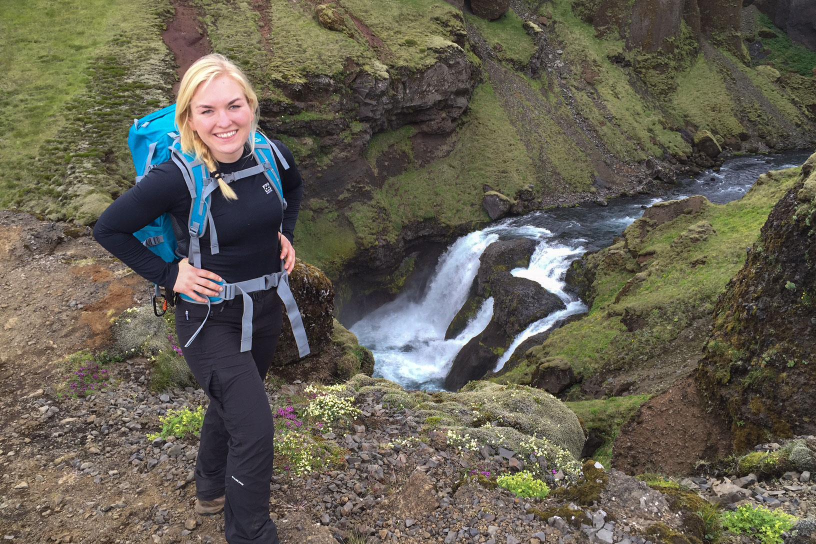 Woman smiling for picture with backpack with river from Fimmvorduhals Trail in background