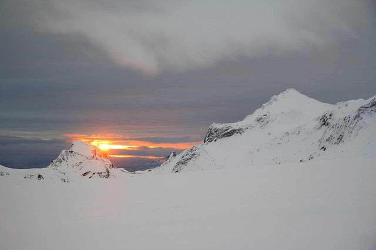 Sunset next to mountains covered with snow