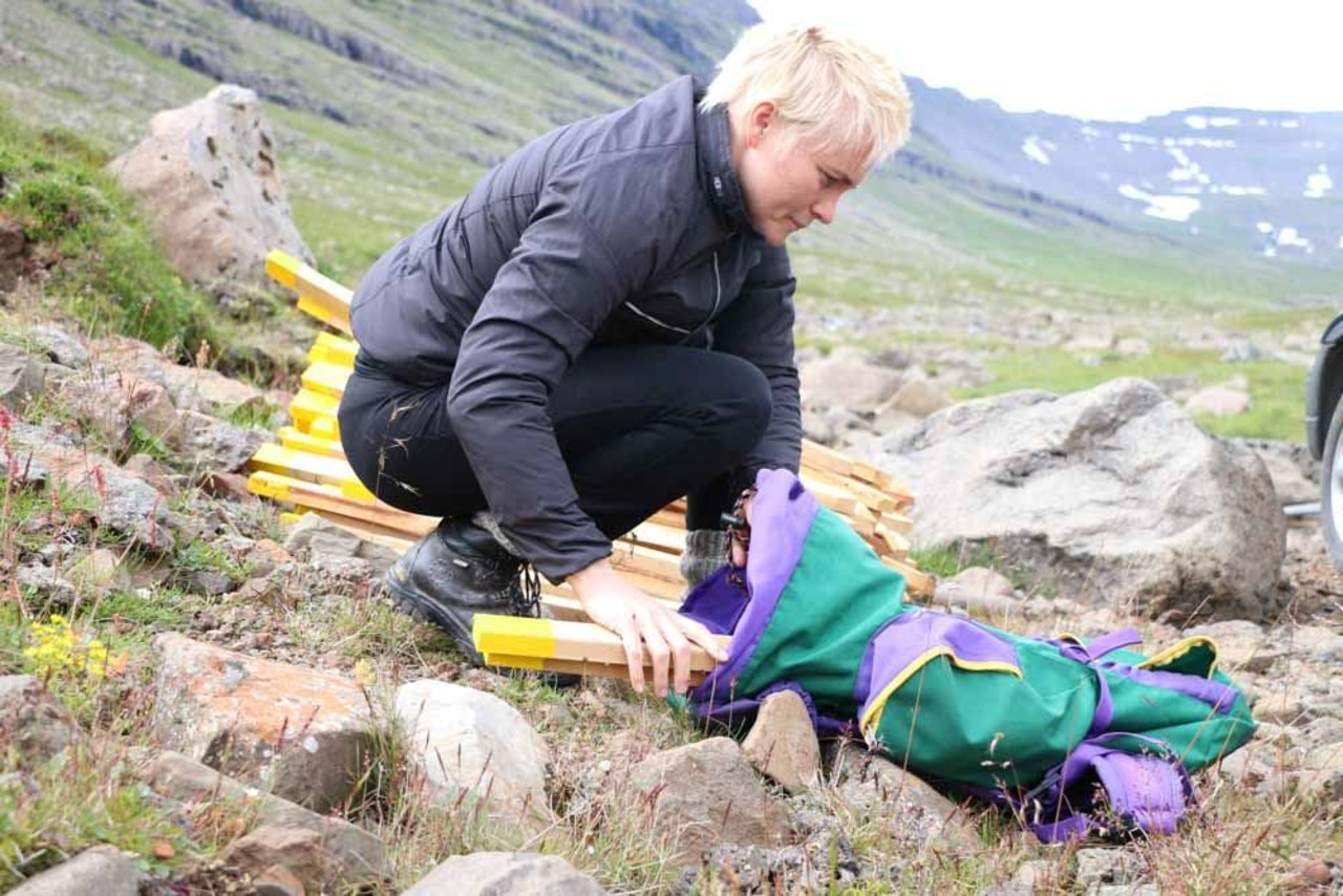 A girl getting the pegs ready for setting to mark a hiking trail for Icelandic Mountain Guides in Iceland