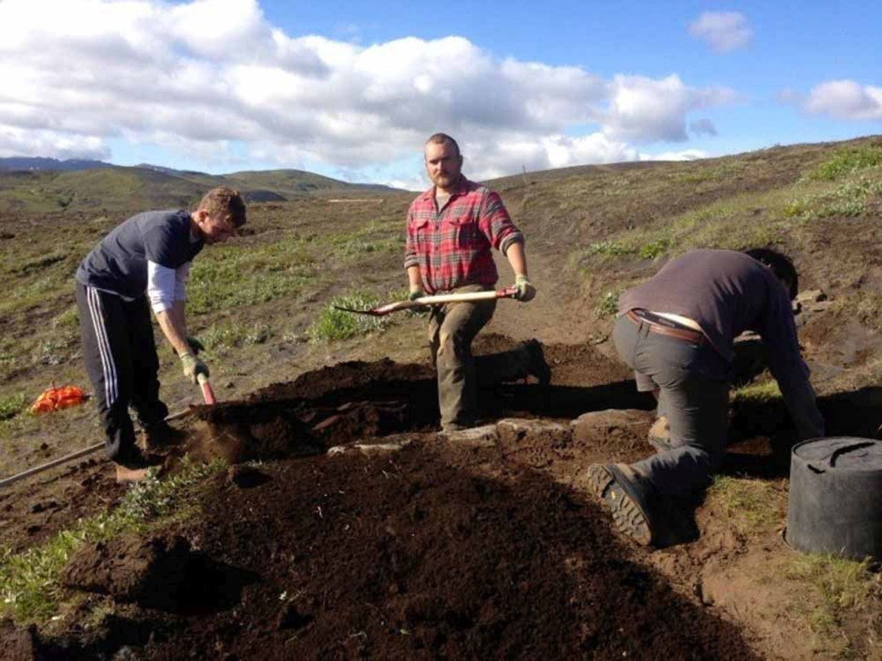 Three men working hard on digging in Iceland