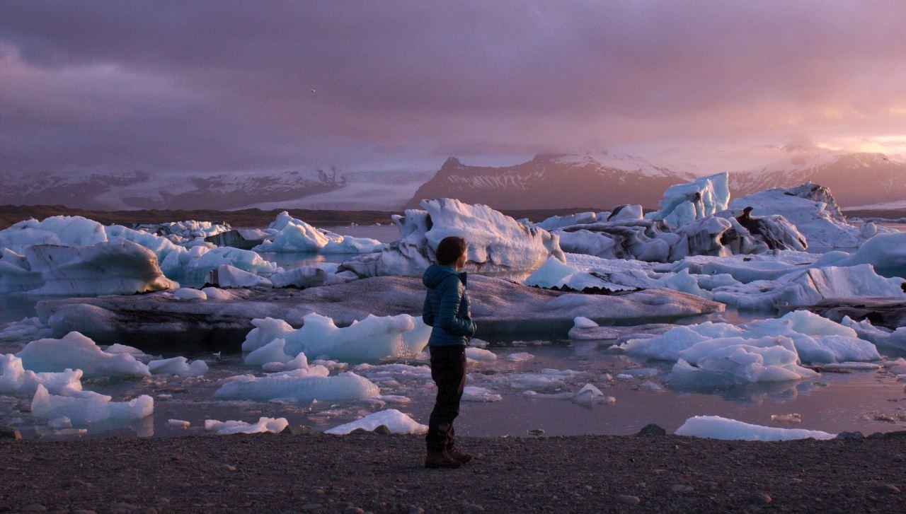 A woman standing on a rocky beach on a summers eve at Jökulsárlón on a tour with Icelandic Mountain Guidis