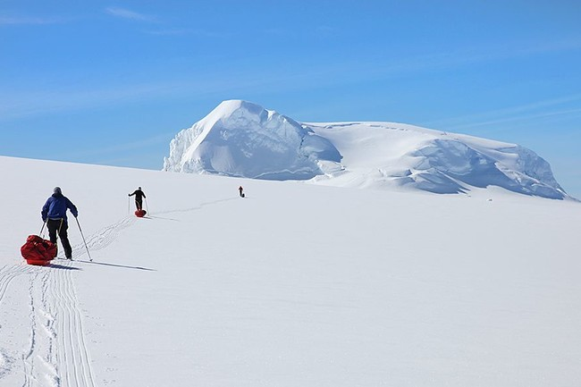Three mountaineers crossing a snowy hill on Vatnajökull glacier on a tour with Icelandic Mountain Guides