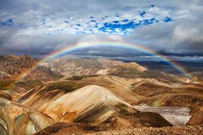 A rainbow over rhyolite mountains in the highlands on the Laugavegur trail. One of many of our Iceland hiking tours.
