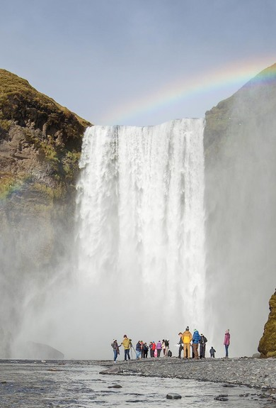 People admiring Skogafoss (Skógafoss) waterfall in Iceland with rainbow shining across the waterfall