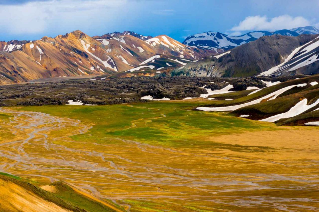 The colorful rhyolite mountains in Landamannalaugar and green field and river.