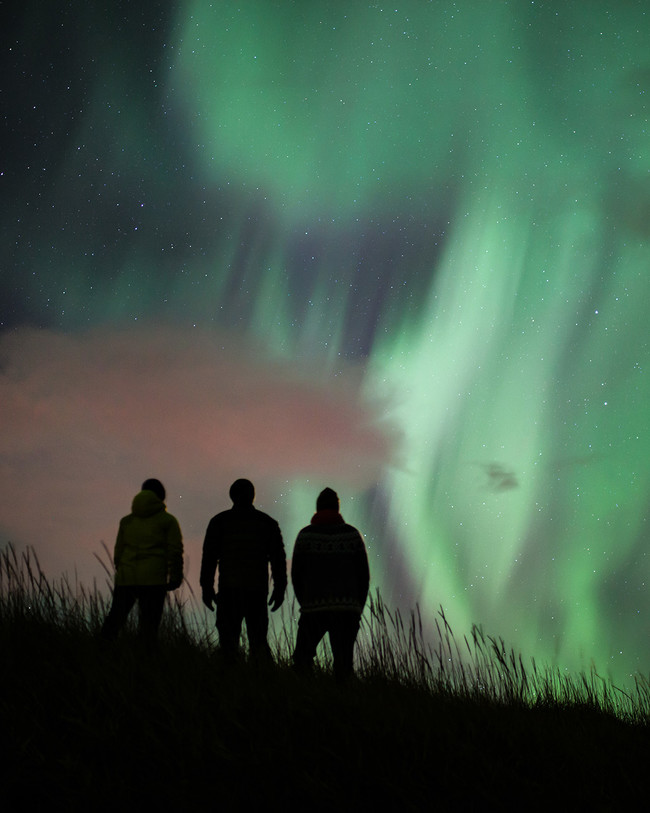 Three silhouettes of people admiring green Iceland Northern Lights at night