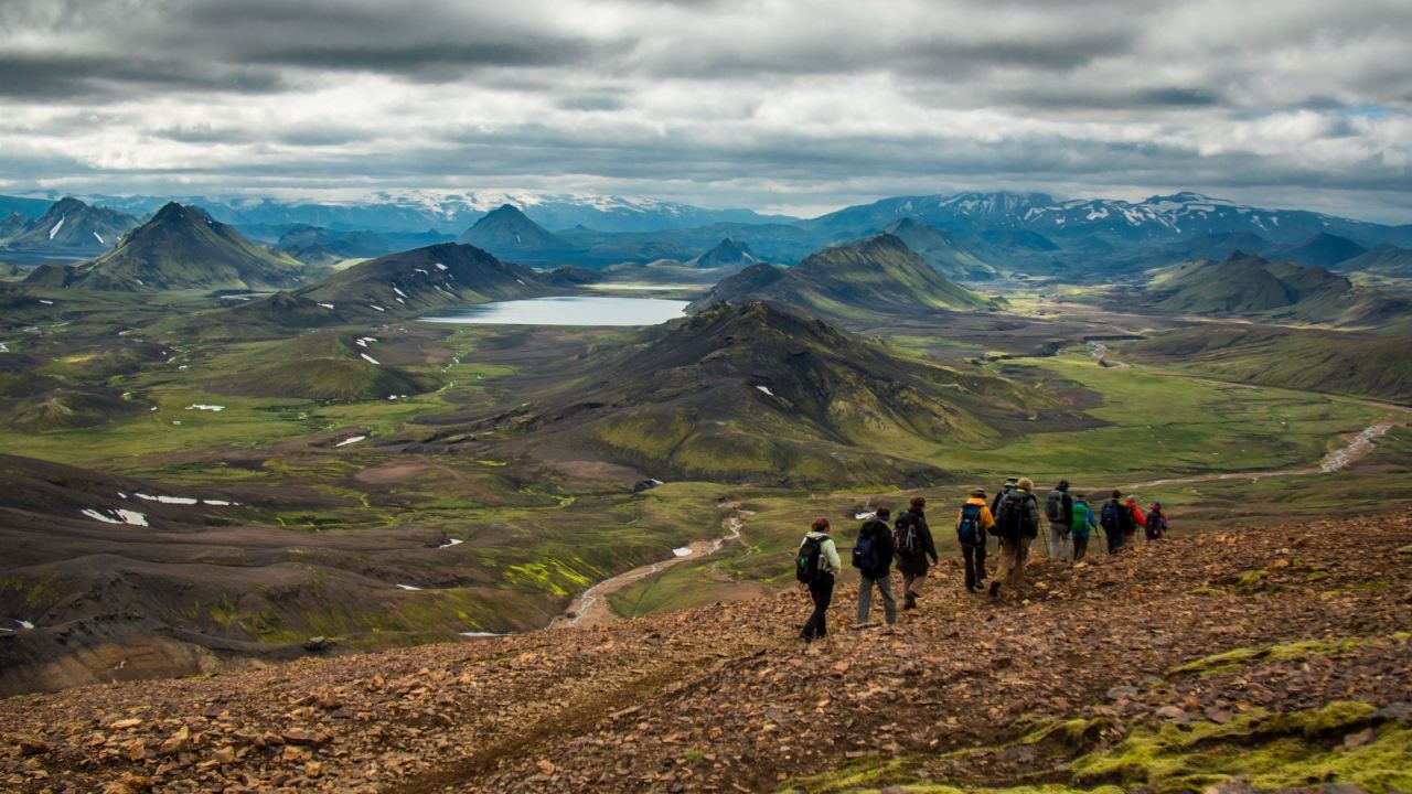 A group of people hiking toward green and black mountains in Iceland. Iceland hiking tours feature the best of the highlands.