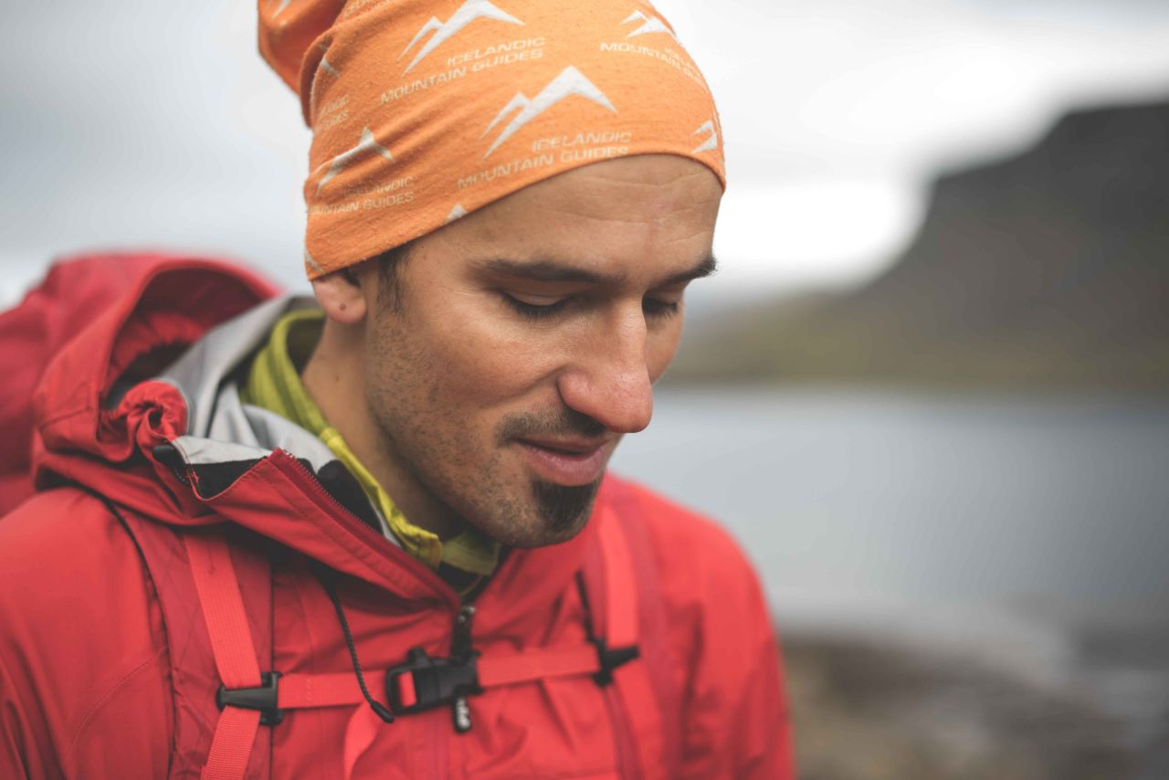 A man wearing a red jacket and an orange hat marked Icelandic Mountain Guides