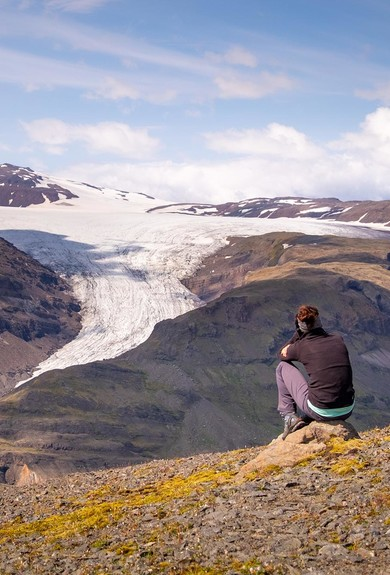 A hiker looking at an outlet glacier flowing down from the ice cap in the distance