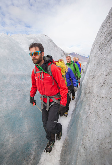 Icelandic mountain guide leading people through a crevasse in svinafellsjokull