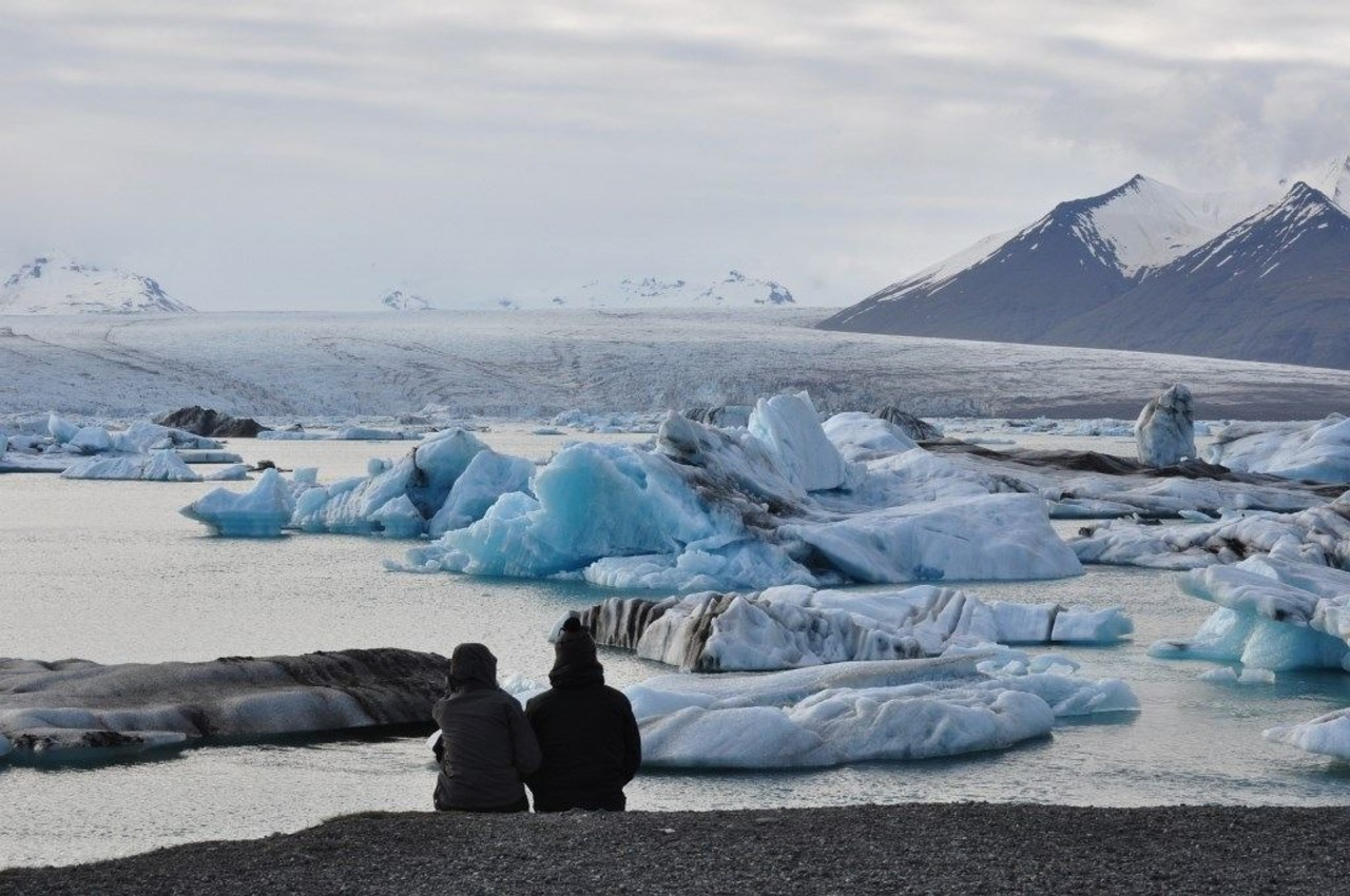 People admiring the ice bergs in Jökulsárlónwith snowy mountains in background