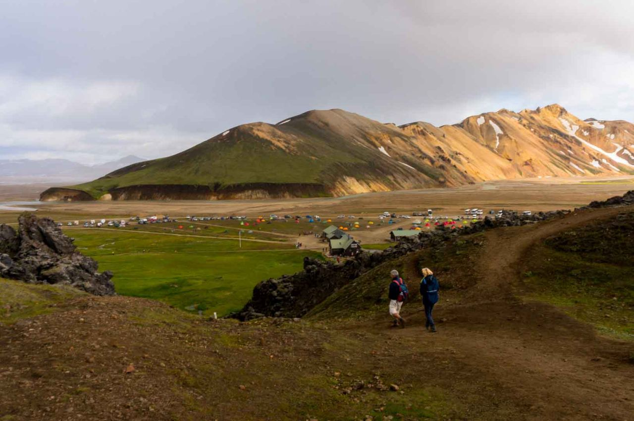 Two people walking toward the camping grounds in Landmannalaugar in the Icelandic highlands